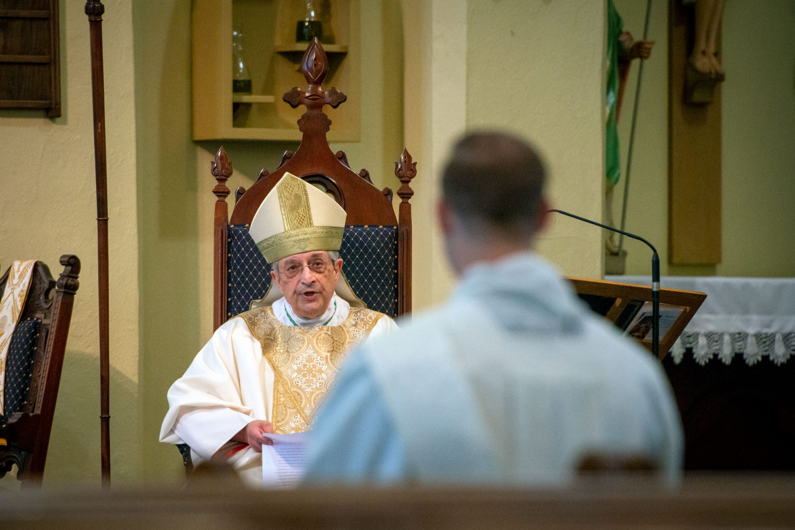 Father Martuscello listens as Bishop Matano delivers the homily.