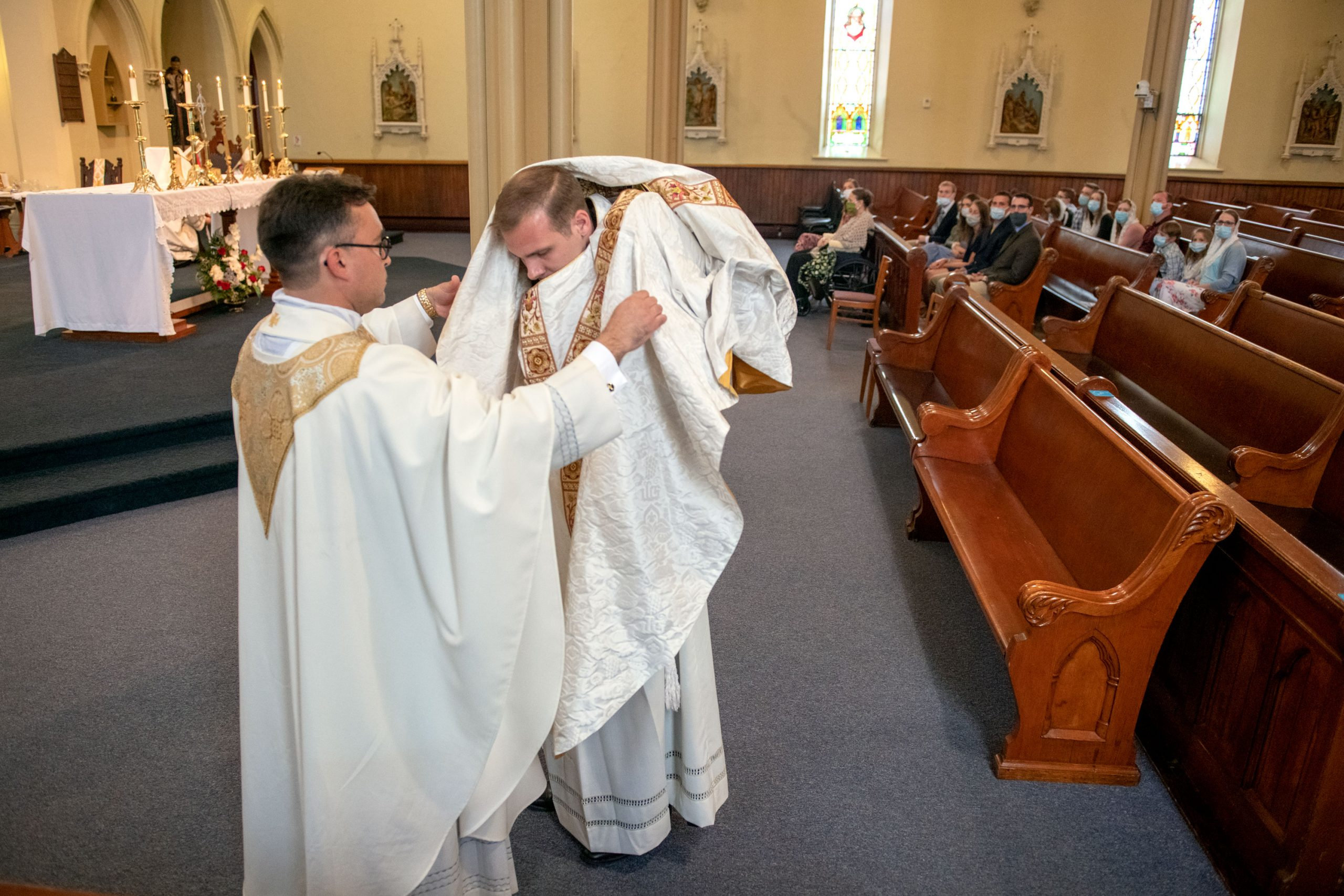 Father Martuscello is vested by Father Jones.