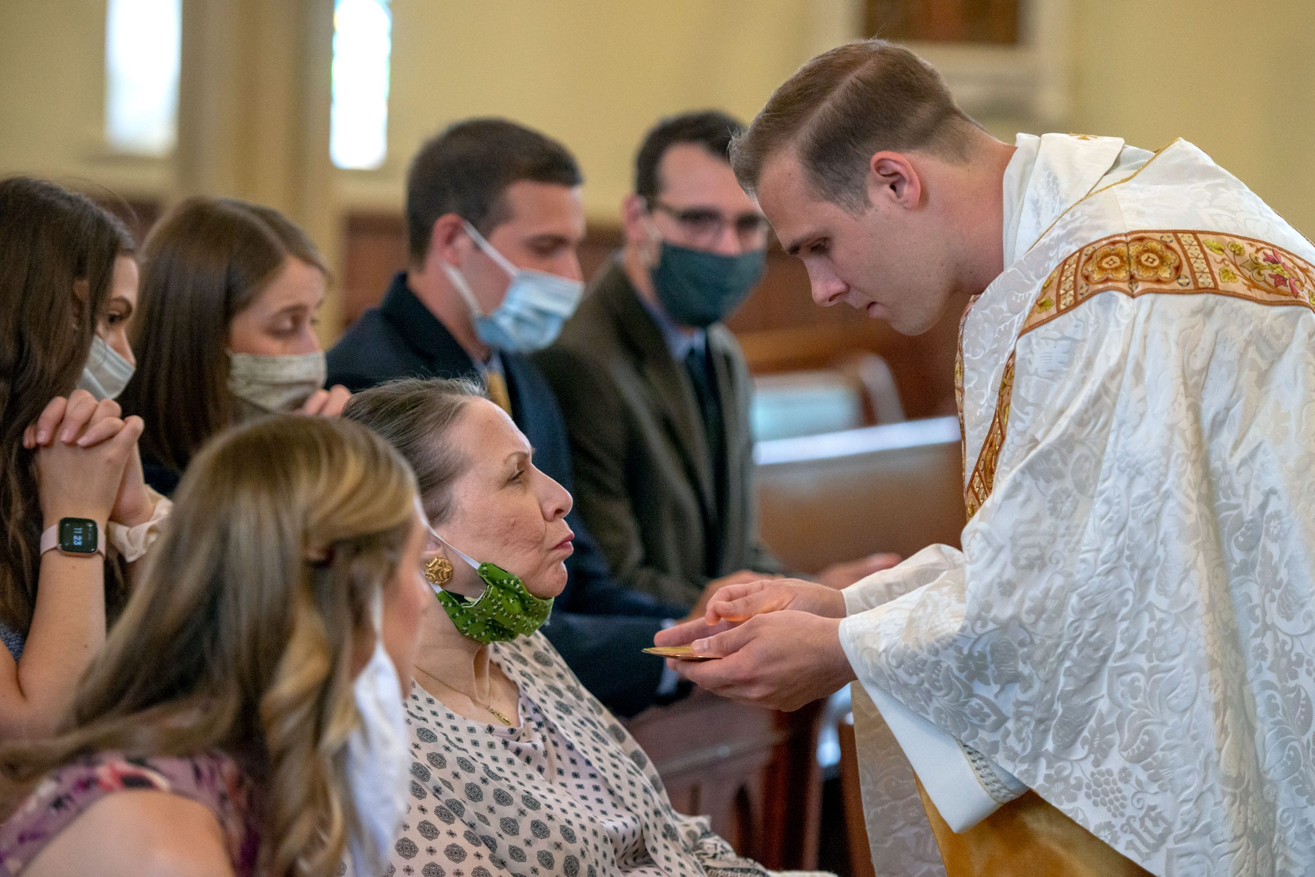 Father Martuscello gives communion to his mother, Mary.