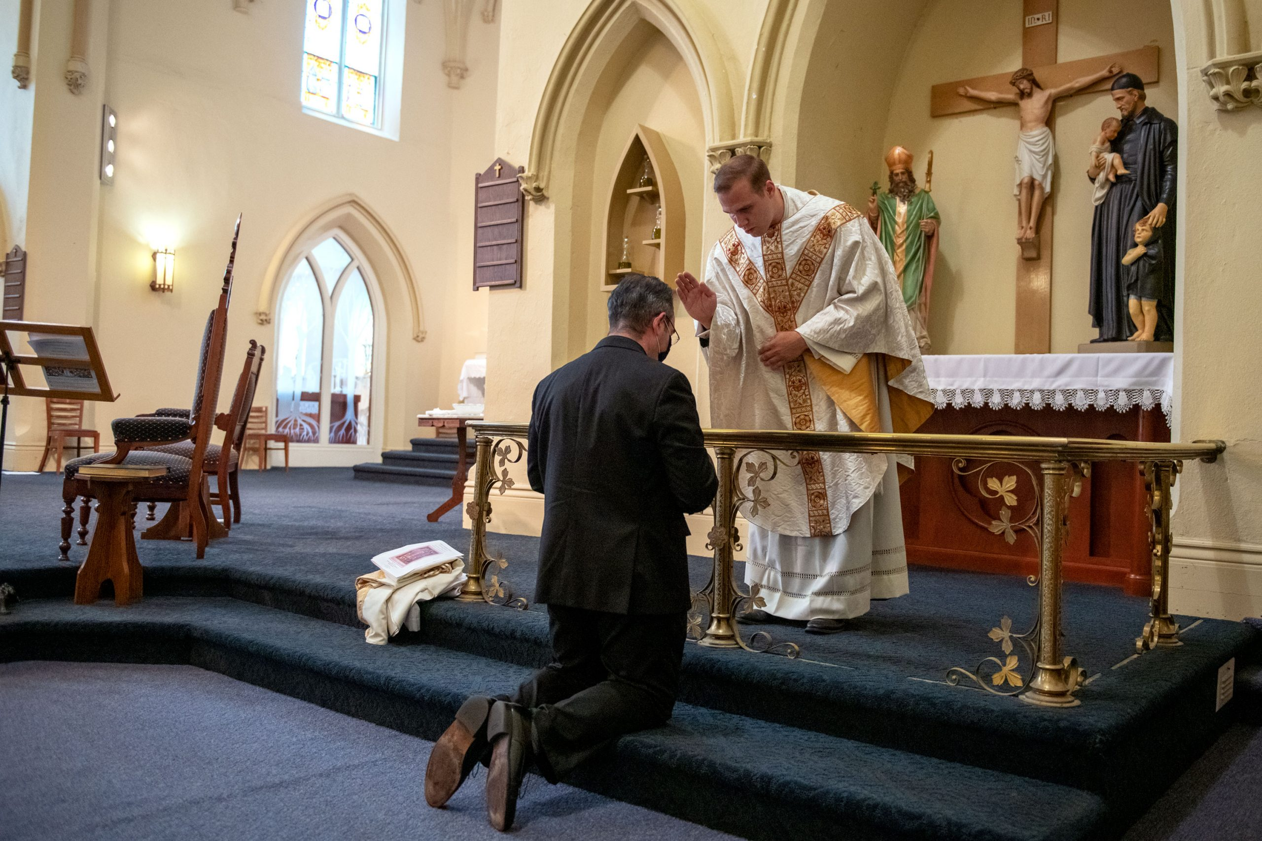 Father William Coffas receives a blessing from Father Martuscello.