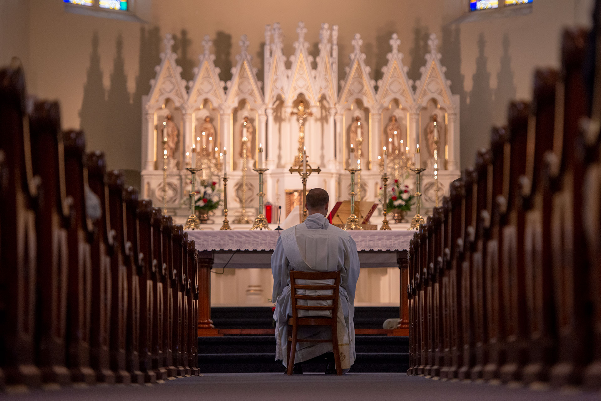 Father Martuscello sits before the altar.