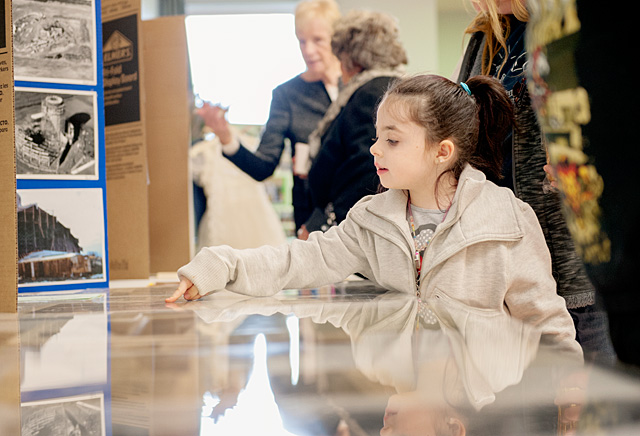 Five-year-old Abigail Grinnell, 5, whose family has been going to Greece's St. John the Evangelist Parish for more than 50 years, looks at a display on the parish's history Nov. 23.