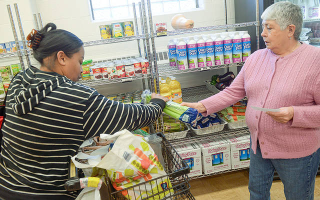 <p>Perdomo Carmen, right, helps Tammy Liddell as she receives food at the Sister Regis Food Cupboard on Nov. 19, 2018 in Rochester. (Courier Photo by John Haeger)  </p>