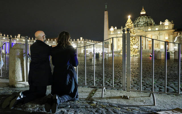 <p>People pray outside St. Peter&rsquo;s Square during the Christmas Eve Mass celebrated by Pope Francis at the Vatican Dec. 24. The Mass was not open to the general public and began at 7:30 p.m. local time so that the limited number of attendees could return home in time to observe Italy&rsquo;s 10 p.m. curfew. (CNS photo by Guglielmo Mangiapane/Reuters)  </p>