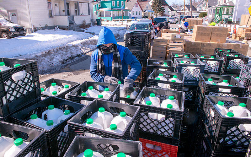 <p>Volunteer Allen Griffith passes out Upstate Farms milk during a Feb. 25 Foodlink distribution in Rochester. The milk was supplied through the Nourish New York initiative.