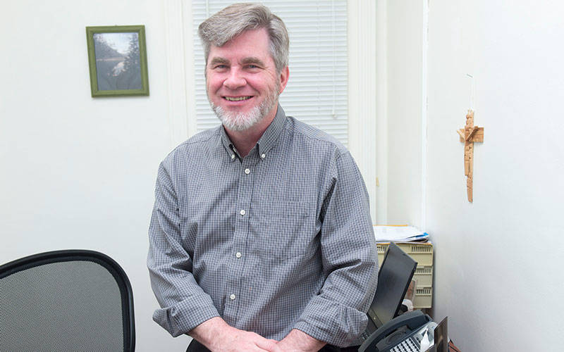 <p>Deacon Greg Kiley poses in his office at Catholic Charities in Geneva.