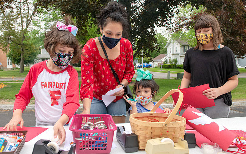 <p>Lili Crowe (from left), Maria Crowe and Jem Crowe participate in one of the craft stations during the Pentecost Family Festival May 23 at Church of the Assumption in Fairport. (Courier photo by Jeff Witherow)  </p>