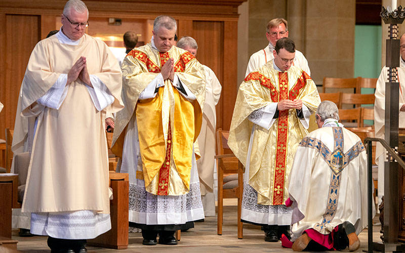 <p>Bishop Salvatore R. Matano receives a blessing from Father Joseph Maurici at the conclusion of the June 5 Solemn Mass of Ordination, while Deacon Edward Giblin (left) and Father Steven Lewis (center) bow their heads.  </p>