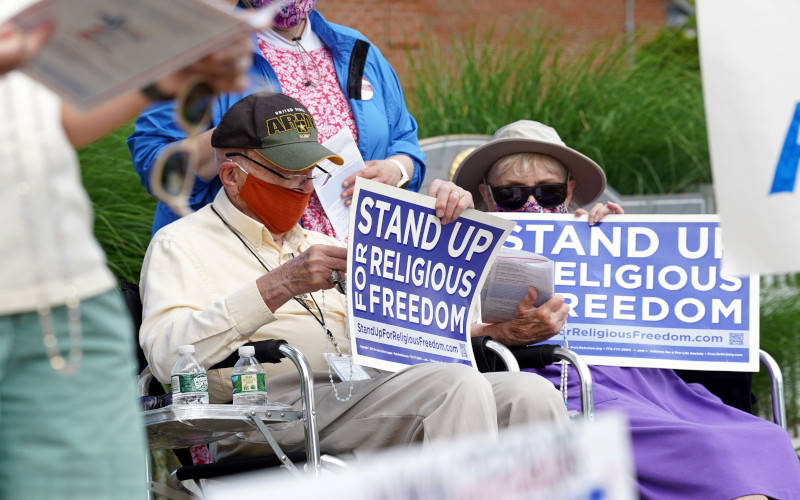 <p>Eric and Anne Waxman recite the rosary while participating in a roadside prayer rally marking Religious Freedom Week at St. James Church in Setauket, N.Y., June 24, 2020. (CNS photo by Gregory A. Shemitz)  </p>