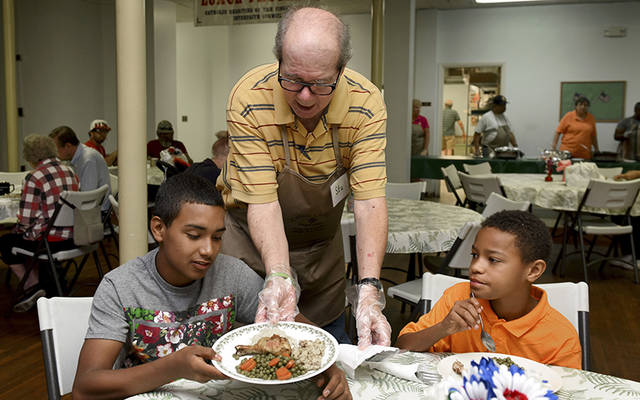 <p>The Geneva Community Lunch Program, a ministry of Catholic Charities of the Finger Lakes, serves about 14,000 free meals a year. Above, coordinator Stu Einstein serves lunch to Aneudi Rivera, 15, and James Taylor, 11 in June 2016.  </p>
