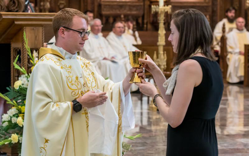 A newly ordained priest distributes Communion. One of the challenges facing a newly ordained priest is that things in ministry are not always like what they had learned in seminary. (CNS photo by Joe Romie/Today's Catholic)