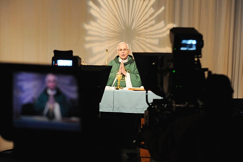 Father Thomas Mull is framed by cameras as he celebrates Mass in the Channel 10 WHEC-TV studios in rochester Nov. 3. The priest has been celebrating the televised Masses since 1982.