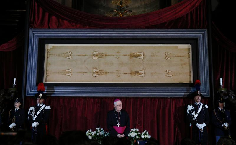 Archbishop Cesare Nosiglia of Turin, papal custodian of the Shroud of Turin, stands in front of the shroud during a preview for journalists in the Cathedral of St. John the Baptist in Turin, Italy, April 18.