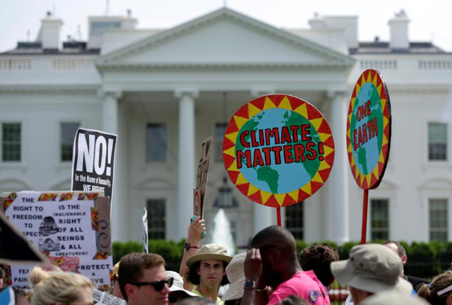 Protesters carry signs during the People's Climate March April 29 outside the White House in Washington. The U.S. bishops June 1 urged President Donald Trump to honor the nation's commitment to the Paris climate pact and protect the planet.