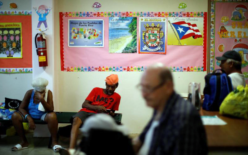 """People rest in a school used as a shelter before the arrival of the Hurricane Maria Sept. 19 in Guayama, Puerto Rico. Hurricane Maria has made landfall in Puerto Rico, bringing """"catastrophic"""" 155mph winds and dangerous storm surges, after battering the Virgin Islands."""