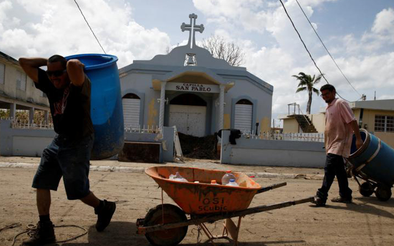 Men carry a container filled with water past a damaged church Sept. 24 after the area was hit by Hurricane Maria in Toa Baja, Puerto Rico.