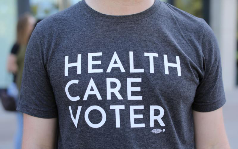A protester wears a T-shirt at an Oct. 12 SoCal Health Care Coalition protest at the University of California San Diego in La Jolla, Calif.
