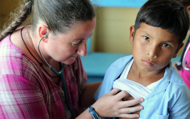 Mercy Sister Karen Schneider, assistant professor of pediatric emergency medicine at Johns Hopkins University in Baltimore, examines a boy in 2017 at a makeshift clinic in a remote area of Guyana. Everyone should have access to essential health services and no one should have to fall into poverty to obtain needed care, a Vatican representative said. (CNS photo by Bob Roller)