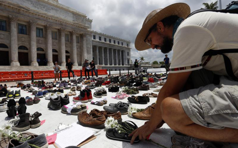 A man in San Juan, Puerto Rico, places a pair of sandals in front of the capitol building June 1 to represent those killed by Hurricane Maria. (CNS photo by Thais Llorca/EPA)