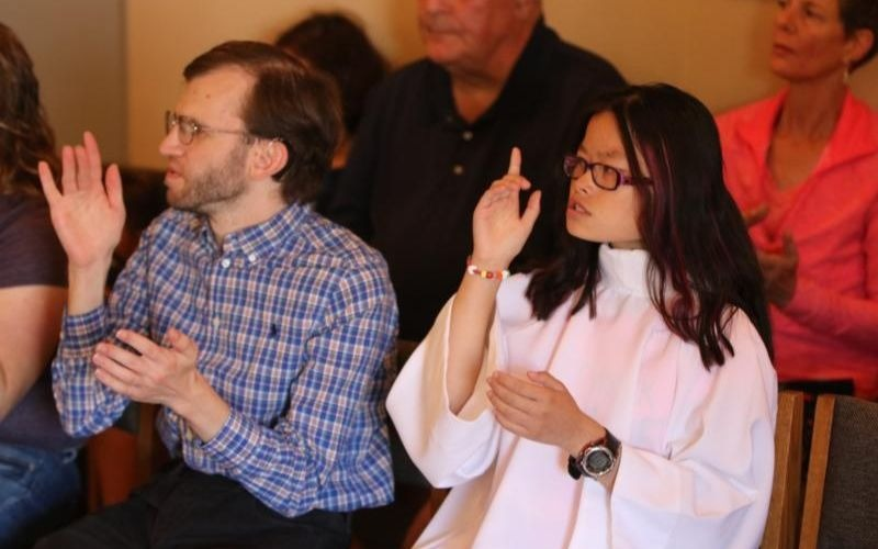 """Christopher Sloan and Sophia Jo Peters sign the creed during a Mass in sign language in early September in the chapel at St. Peter Parish in Portland, Ore. """"When you come here you feel peace. Why? Because you know we understand your struggles in life,"""" fellow worshipper Tim Blade said. (CNS photo by Ed Langlois/Catholic Sentinel)"""