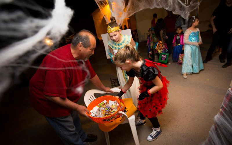 """Children pick out treats during a Halloween carnival in 2014 at Santa Cruz Catholic School in Tucson, Ariz. Halloween is an opportunity for Catholics """"to express in every detail of our observance the beauty and depth of the feast of All Saints,"""" says Bishop David A. Konderla of Tulsa, Okla. Halloween is the eve of All Saints Day, Nov. 1. (CNS photo by Nancy Wiechec)"""