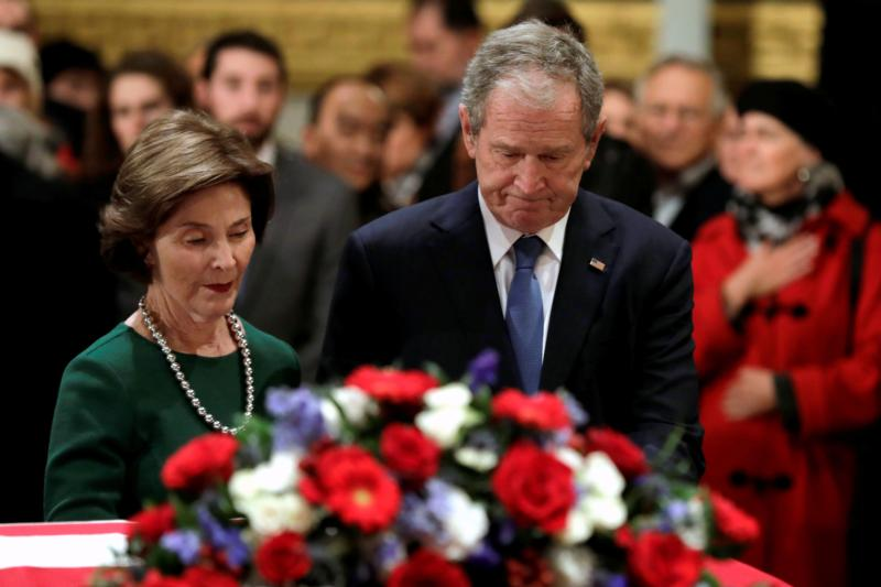 Former U.S. President George W. Bush and former first lady Laura Bush stand at the flag-draped casket of former U.S. President George H.W. Bush as he lies in state inside the U.S. Capitol rotunda Dec. 4 in Washington. George H.W. Bush, the 41st president of the United States, died in his Houston home Nov. 30 at age 94. (CNS photo  by Yuri Gripas/Reuters)
