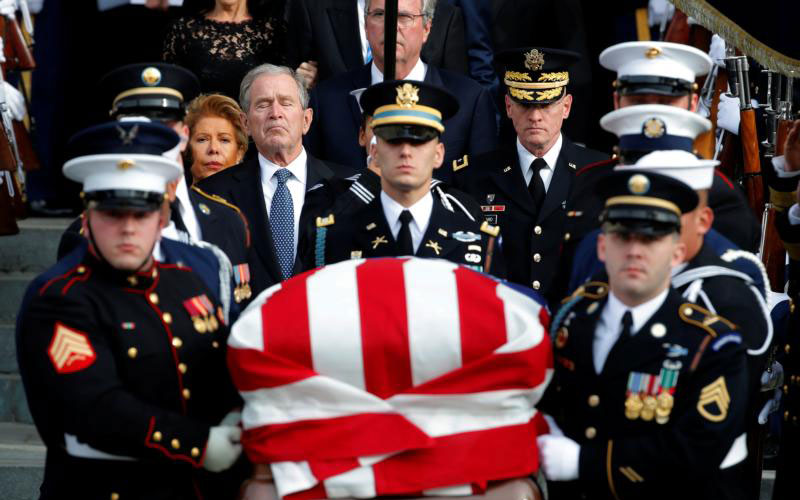 Former U.S. President George W. Bush follows a military honor guard as they carry the flag-draped casket of former President George H.W. Bush after his father's state funeral Dec. 5 at the Episcopal Church's Washington National Cathedral. (CNS photo by Jonathan Ernst/Reuters)
