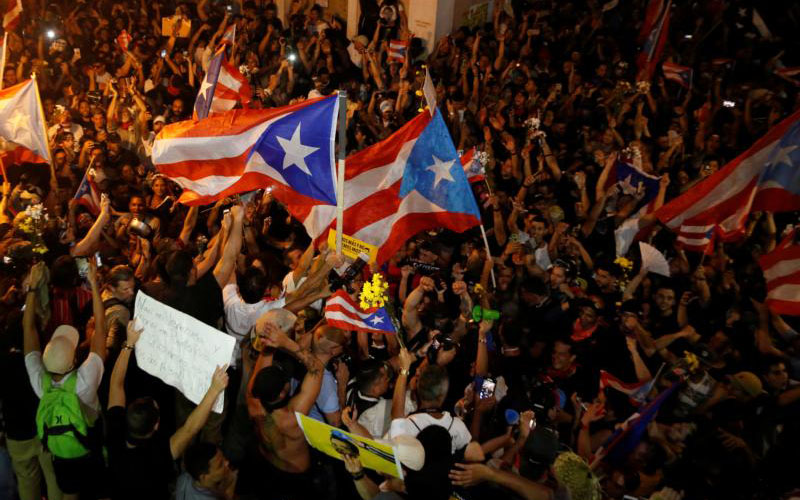 Demonstrators celebrate in the streets of San Juan after Puerto Rican Gov. Ricardo Rossello announced his resignation late July 24, 2019. (CNS photo by Marco Bello, Reuters)