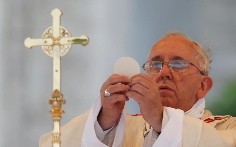 In this 2014 file photo, Pope Francis elevates the Eucharist as he celebrates Mass on the feast of Corpus Christi outside the Basilica of St. John Lateran in Rome.