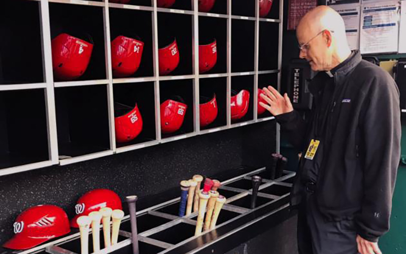 Msgr. Stephen J. Rossetti, a professor at The Catholic University of America and the chaplain for the Washington Nationals, blesses bats before a game during the 2019 season.