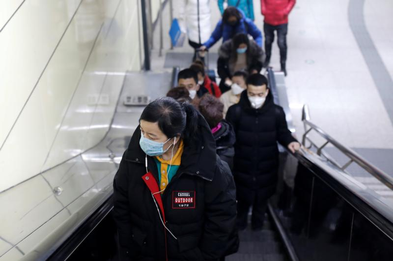 People wearing face masks are seen at the escalator of a Beijing subway station Jan. 27, 2020, as the country is hit by an outbreak of the new coronavirus.The virus has spread to almost every province in mainland China during Lunar New Year.