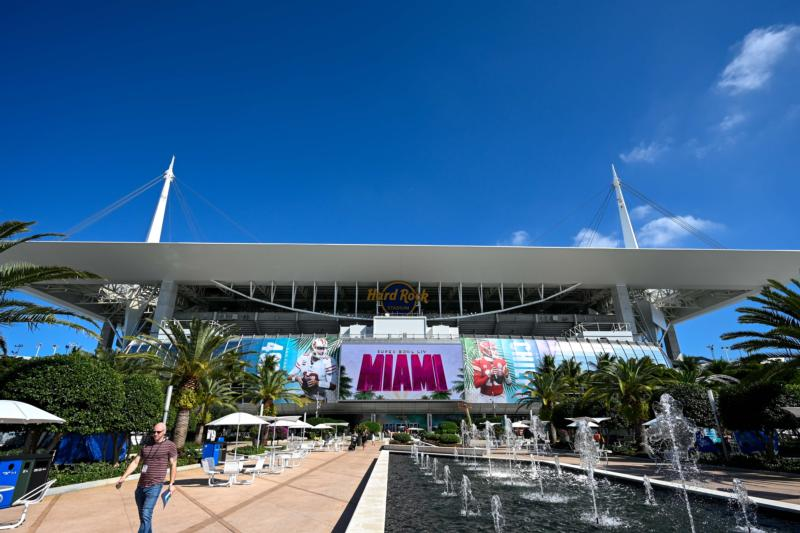 A man walks alongside a fountain outside Hard Rock Stadium in Miami Gardens Jan 28, 2020, where the San Francisco 49ers and Kansas City Chiefs will compete in Super Bowl LIV .