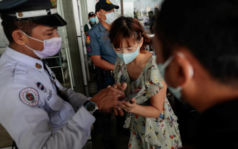 Following confirmed cases of coronavirus in the Philippines, passengers wearing protective masks arrive at the departure area at the Ninoy Aquino International Airport in Manila Feb. 5, 2020.