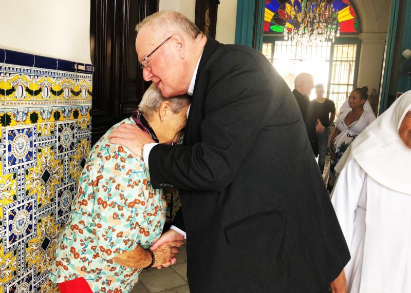 New York Cardinal Timothy M. Dolan hugs an elder at the Hogar Santovenia in Havana Feb. 10, 2020.