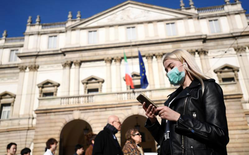 A woman wearing a face mask checks her phone outside the Teatro alla Scala opera house, closed by authorities due to a coronavirus outbreak in Milan Feb. 24, 2020.