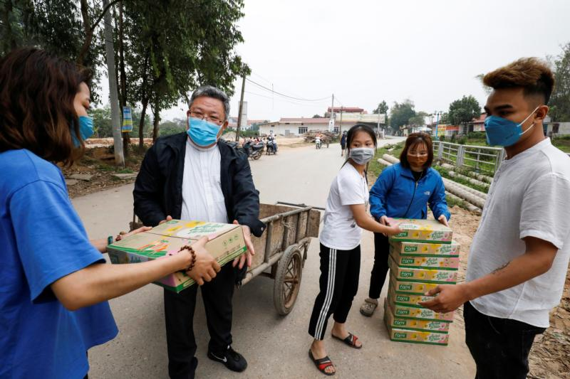 Father Francis Xavier Nguyen Duc Dai distributes food to local people while wearing a protective mask in Son Loi, Vietnam, Feb. 25, 2020.