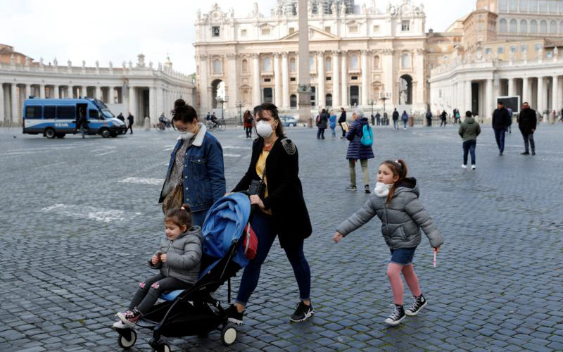 People wear protective face masks in St. Peter's Square after the Vatican reports its first case of coronavirus March 6, 2020.