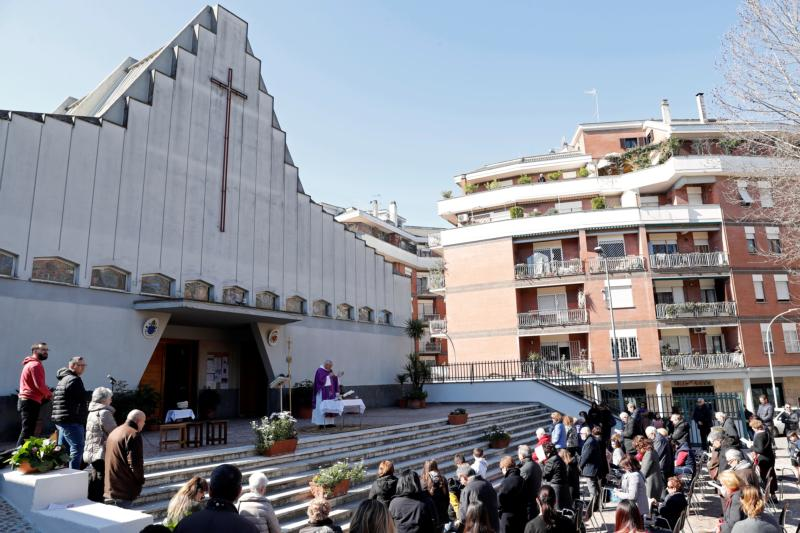 A priest celebrates Mass outside a Rome church March 8, 2020, after Italy's bishops ordered Masses not be held inside in order to contain the coronavirus outbreak.