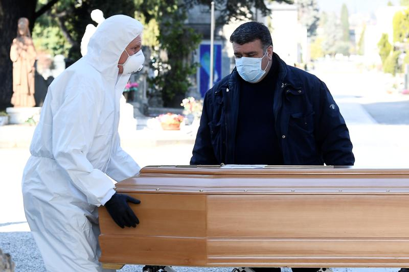 Men in Bergamo, Italy, transport a coffin of a person who died from the coronavirus disease in this photo shot March 16, 2020