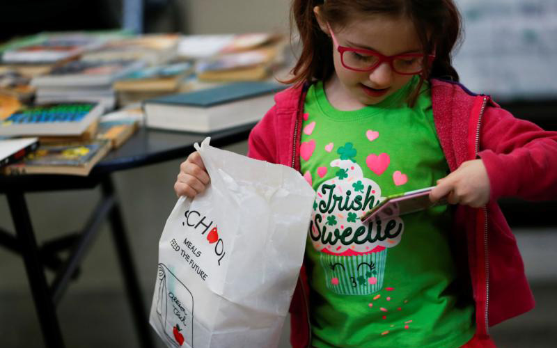 Sammy Kent looks at a free book as she holds her lunch at a student meal distribution site at a Seattle school March 17, 2020.