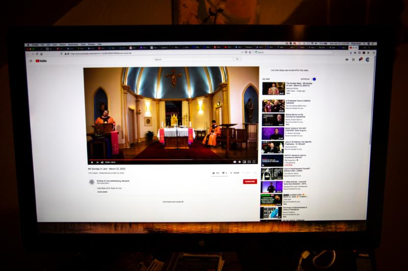 A Maryland Catholic watches from a computer screen a March 22, 2020, livestream Mass, celebrated at St. Rose of Lima Parish in Gaithersburg, Md.