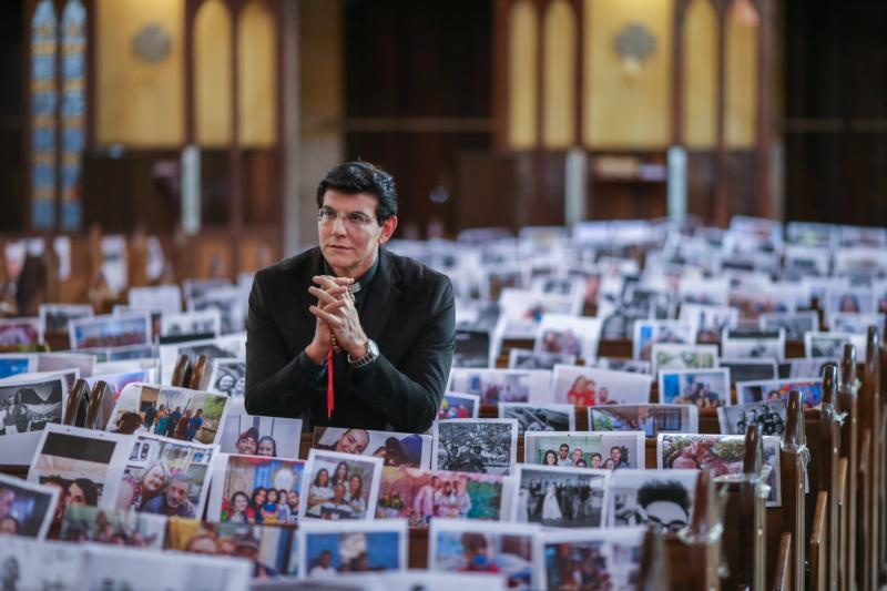 Father Reginaldo Manzotti prays during Mass with photos of his parishioners taped to the pews in the Shrine of Our Lady of Guadalupe in Curitiba, Brazil, March 21, 2020.