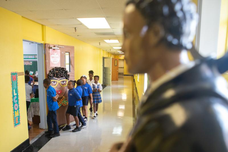Students at St. Mary of the Purification Montessori School in Houston walk by a statue of St. Martin de Porres in this 2019 photo.