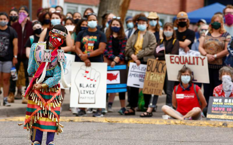 An indigenous girl in Denver dances in traditional dress July 4, 2020, during a march that called on Black, indigenous and Latino communities to rise up against oppression.
