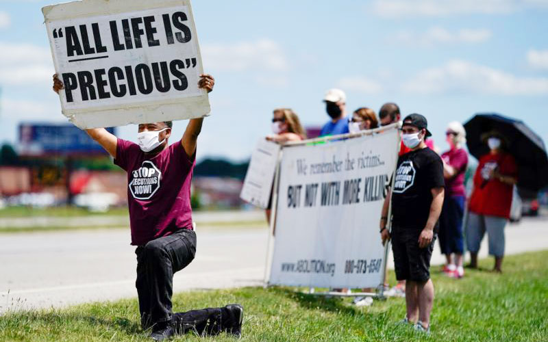 Demonstrators are seen near the Federal Correctional Complex in Terre Haute, Ind., to show their opposition to the death penalty July 13, 2020.
