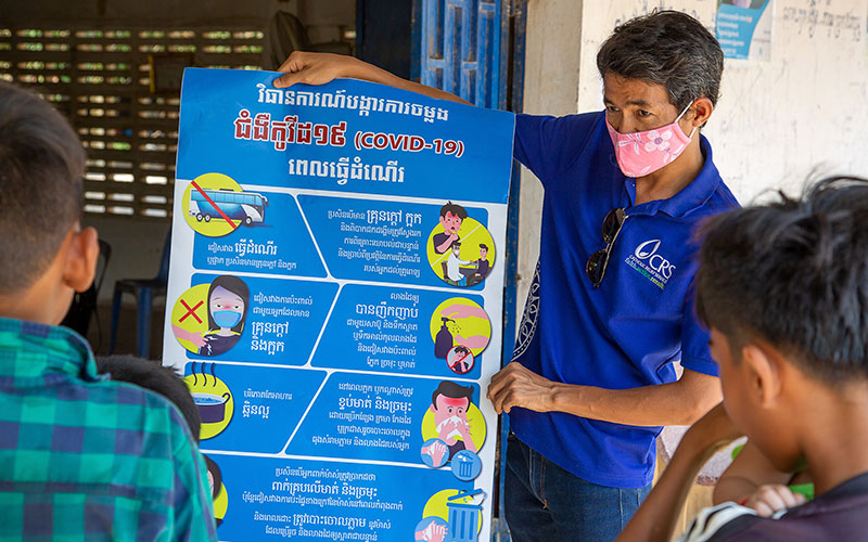 A Catholic Relief Services staff member in Cambodia explains the latest COVID-19 information to a small group of village leaders. (CNS photo by Jennifer Hardy, CRS)