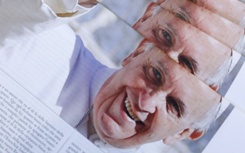 """The front page of L'Osservatore Romano, the Vatican newspaper, pictures Pope Francis with his latest encyclical, """"Fratelli Tutti, on Fraternity and Social Friendship,"""" at the Vatican Oct. 4, 2020."""