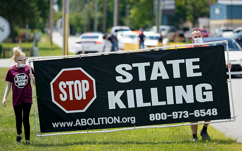 Demonstrators are seen near the Federal Correctional Complex in Terre Haute, Ind., showing their opposition to the death penalty July 13, 2020.