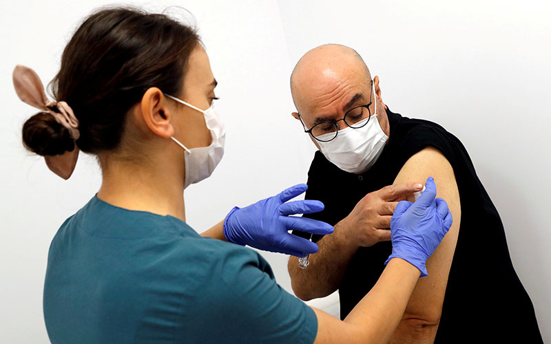A health worker injects a volunteer with an experimental COVID-19 vaccine during Phase III trials in late September at a hospital in Kocaeli, Turkey.