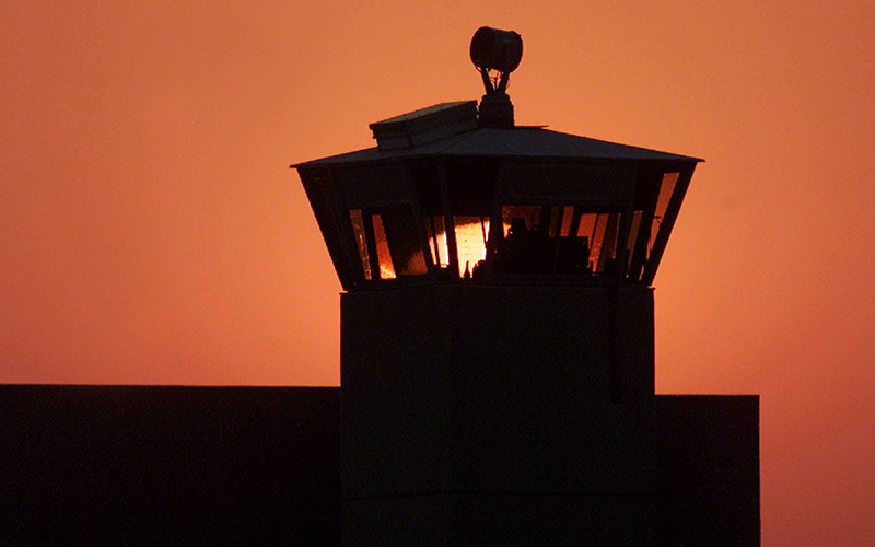 In this file photo, the sun sets behind one of the guard towers at the Federal Correctional Complex in Terre Haute, Ind., June 10, 2001.